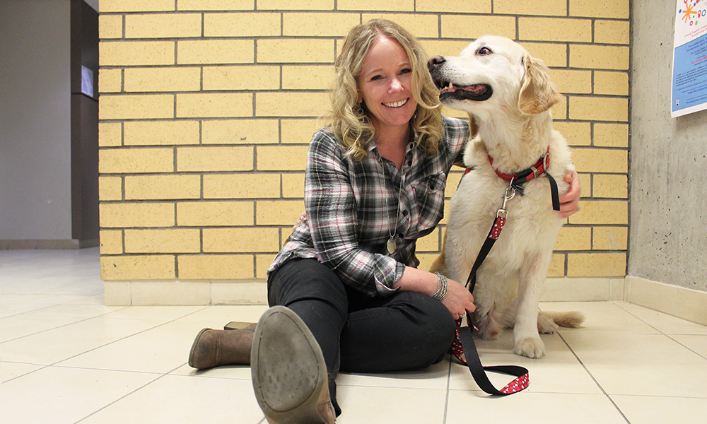 A woman and a golden lab pose for a photo