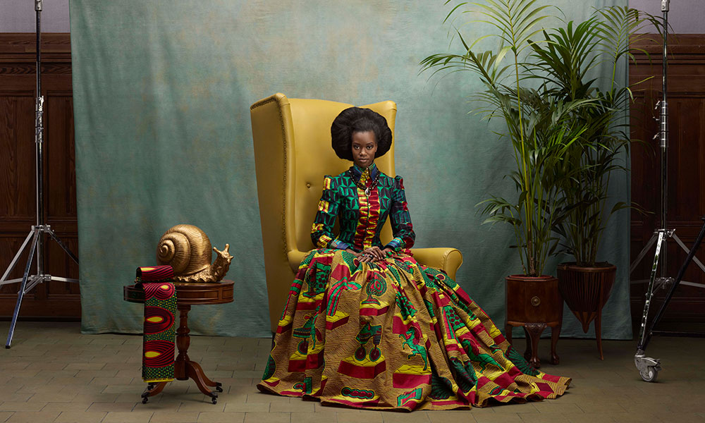 brightly dressed model sit in a large yellow chair