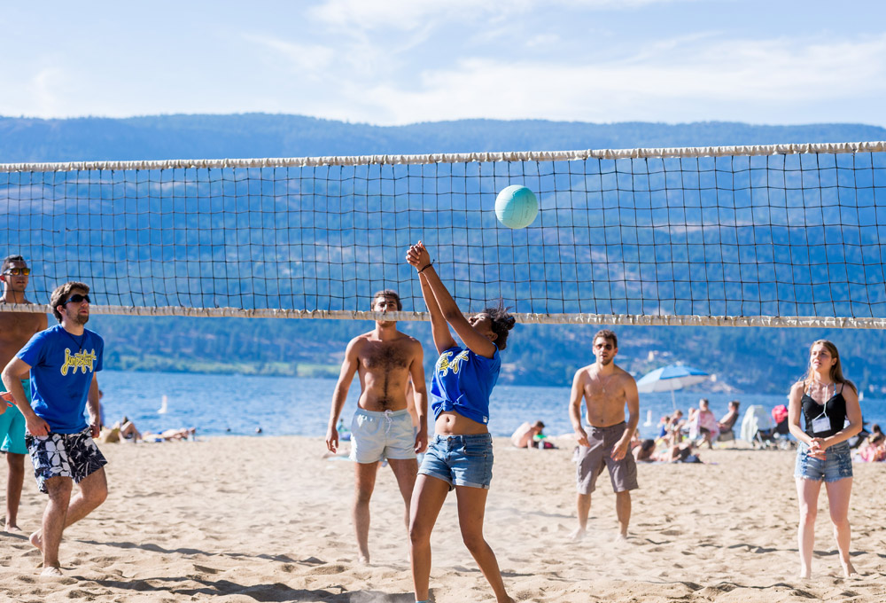 students play beach volleyball by Lake Okanagan.