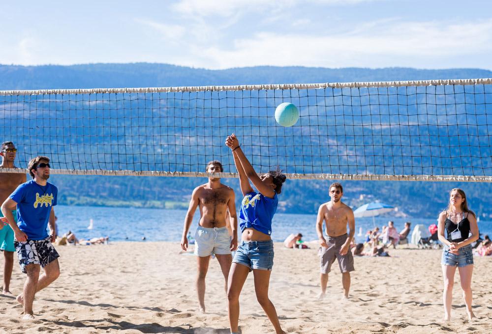 students play beach volleyball by Lake Okanagan.