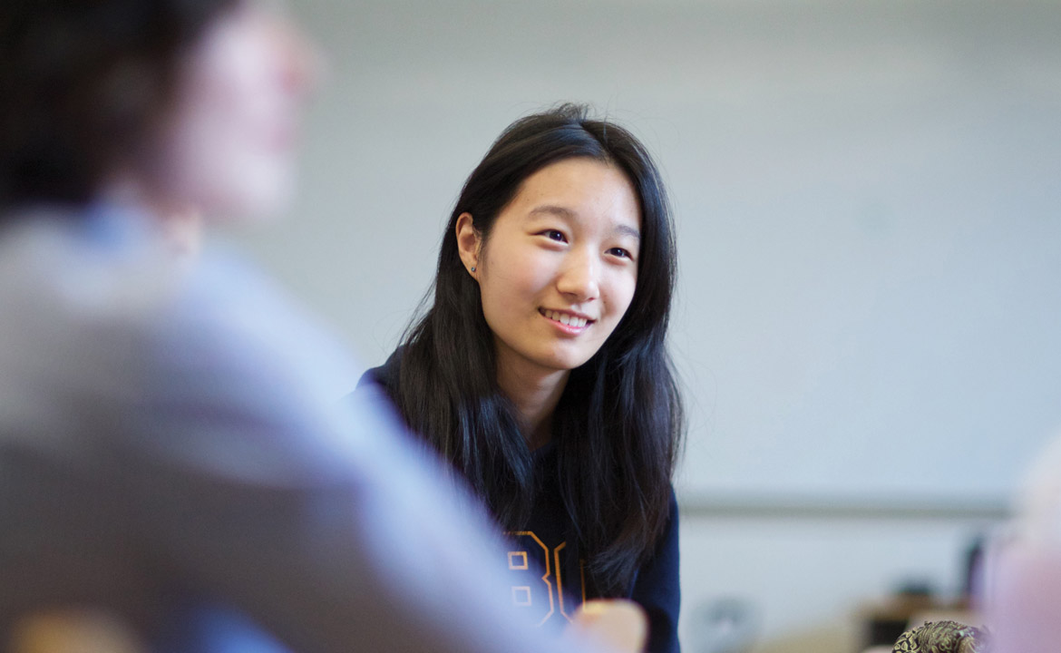 A student in a classroom engaging a small group conversation.