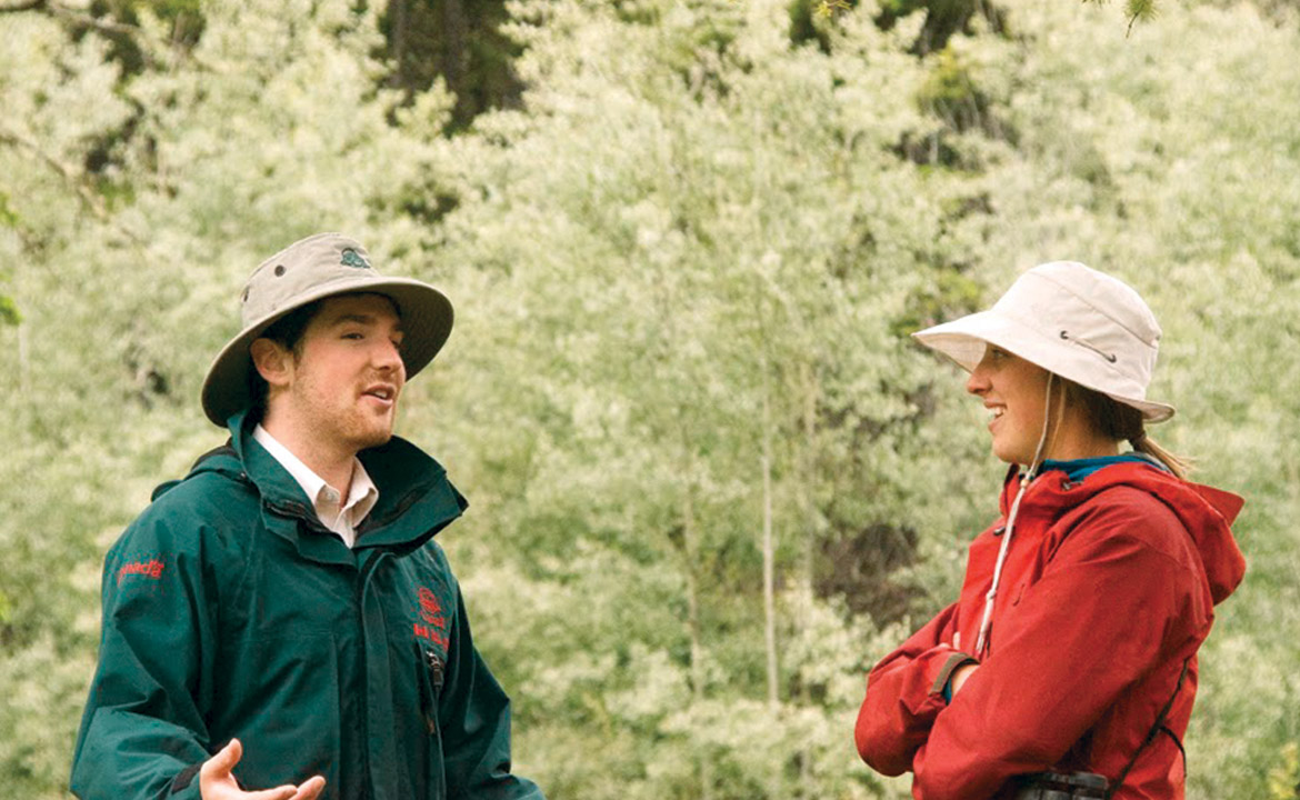 An undergrad student talks with a professor in a forest during a research fieldwork placement.