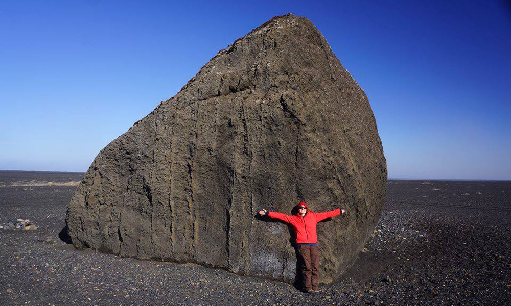 Erica Massey poses on a volcanic glacial outwash with a massive boulder