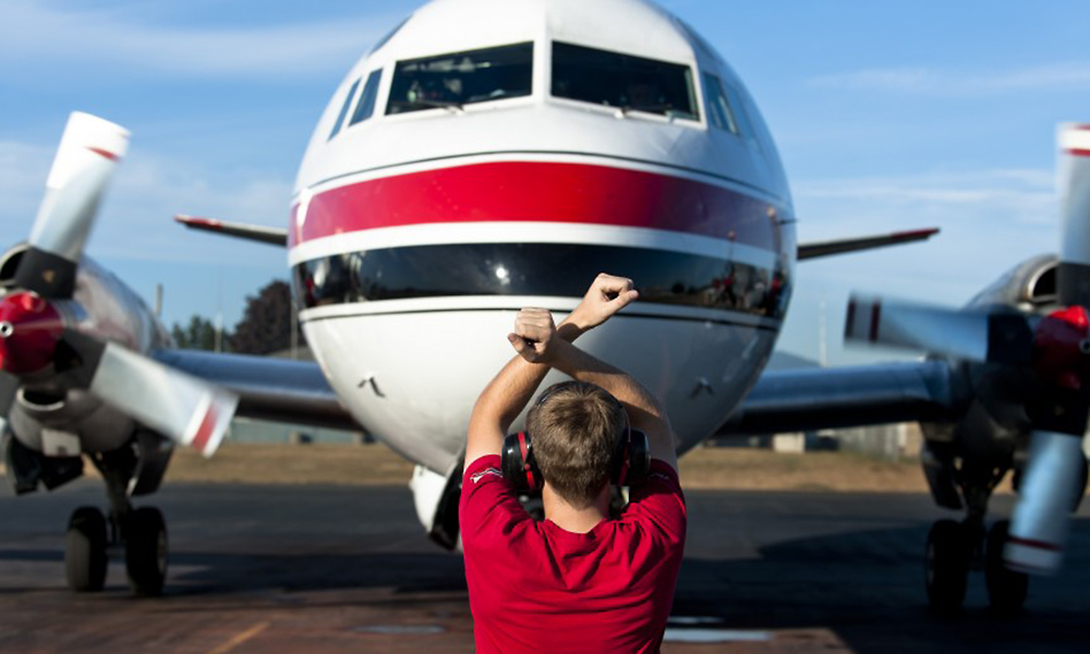 Aircraft marshaller giving direction to a Conair Tanker plane