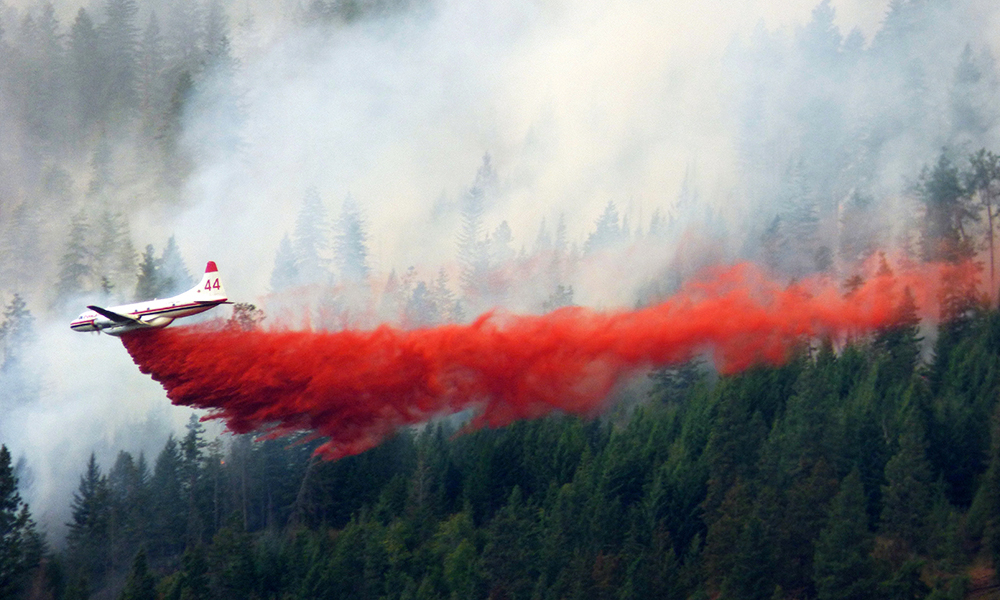 Aircraft dropping red fire retardant on a wildfire