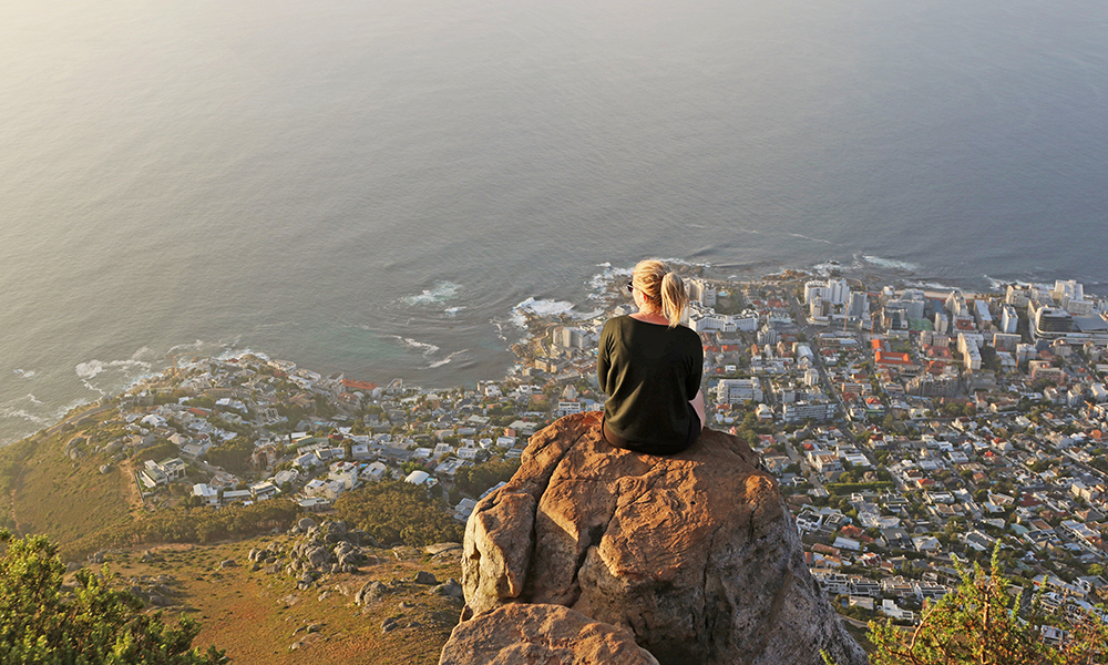 Woman sitting on a rock high above Capetown South Africa