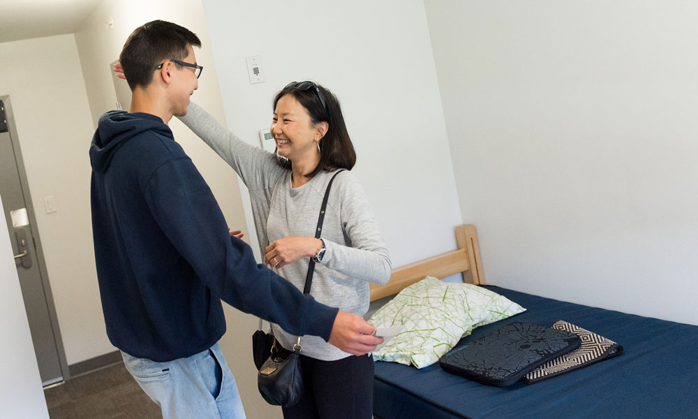 Mother and student hugging in a dorm room