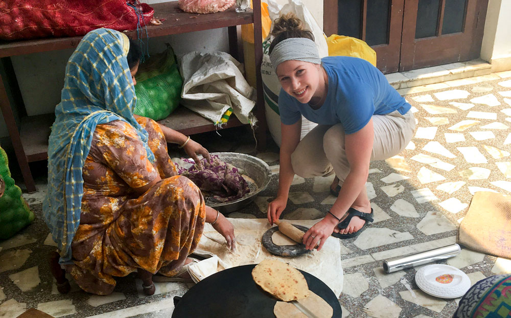 Andres Stinson helps roll dough with a local woman in India.