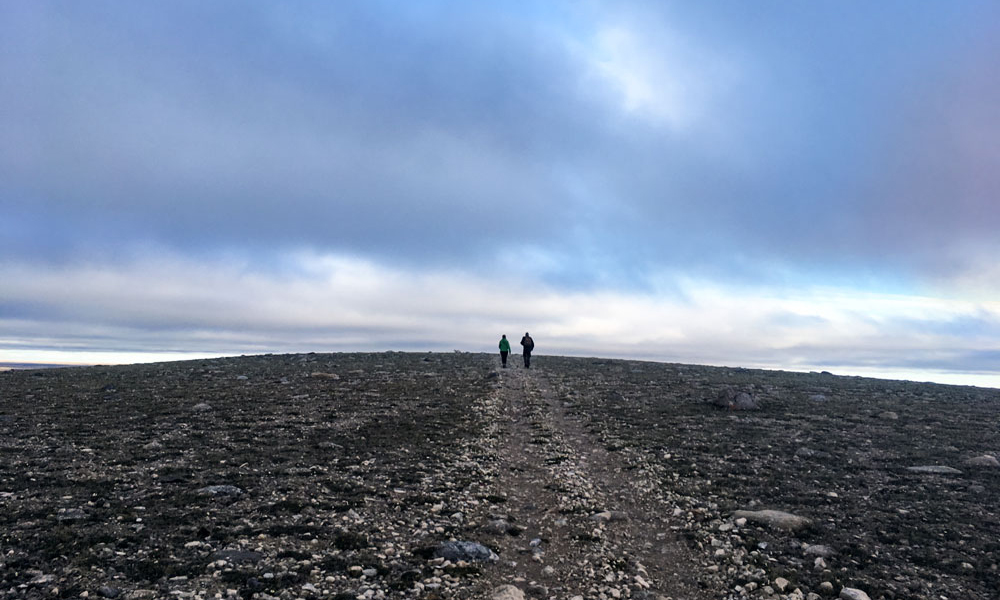 Landscape view of researchers walking across a rocky plane in Nunavut.