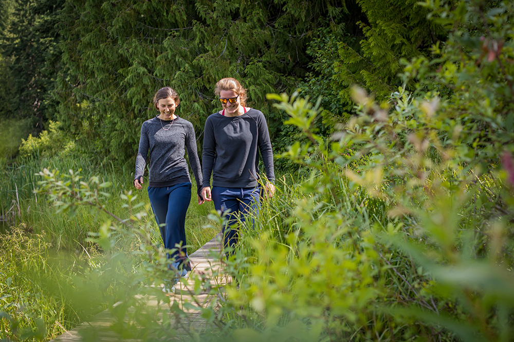 Kelsey Serwa and Brittany Phelan walking along a tree-lined path in Whistler.