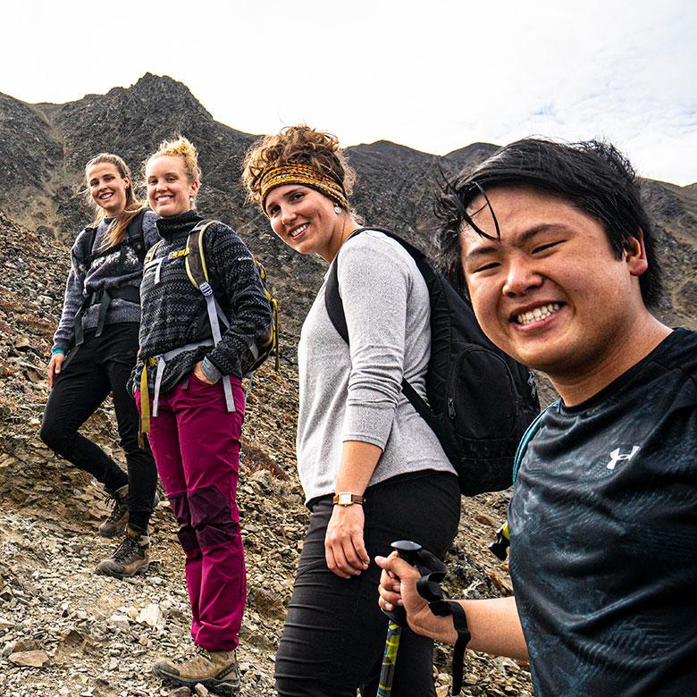 student trekking a mountain in the yukon
