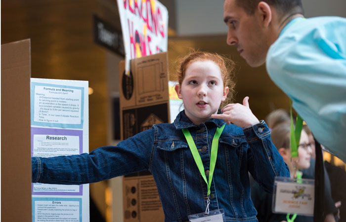 Young girl presenting her poster at the Expo of Awesome science fair