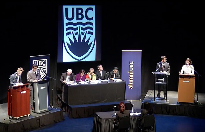 students at podiums on a stage at the Roger Watts debate