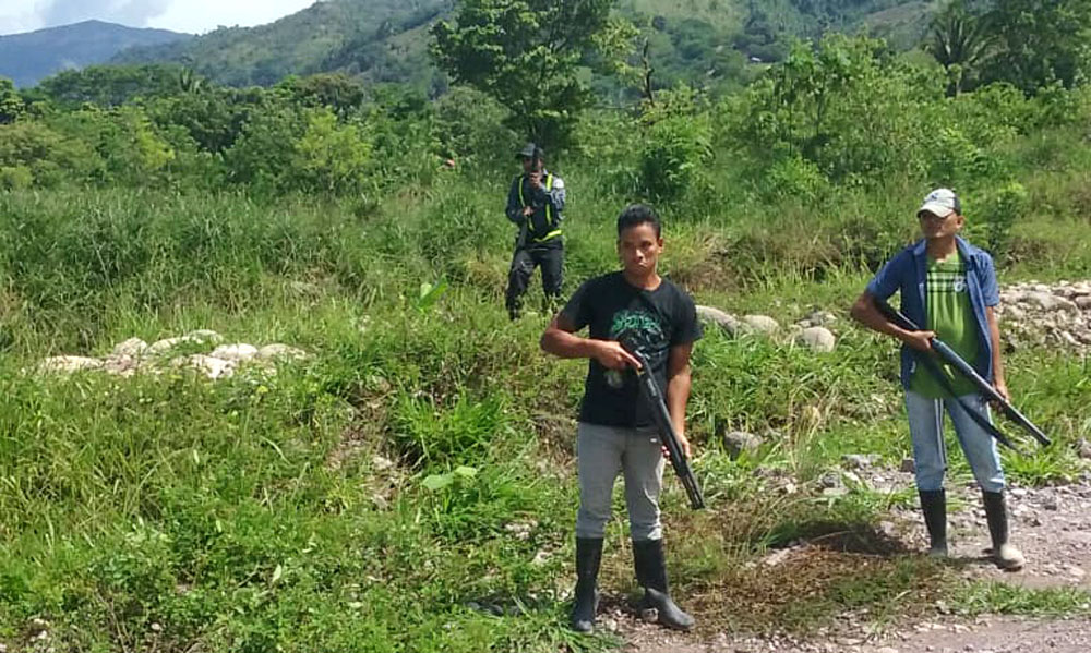 A paramilitary guards access to a local mine in Guapinol, Honduras
