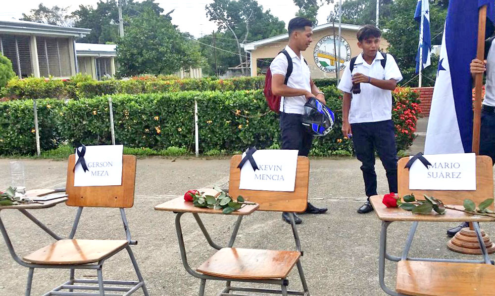 Three empty desks to symbolize students killed