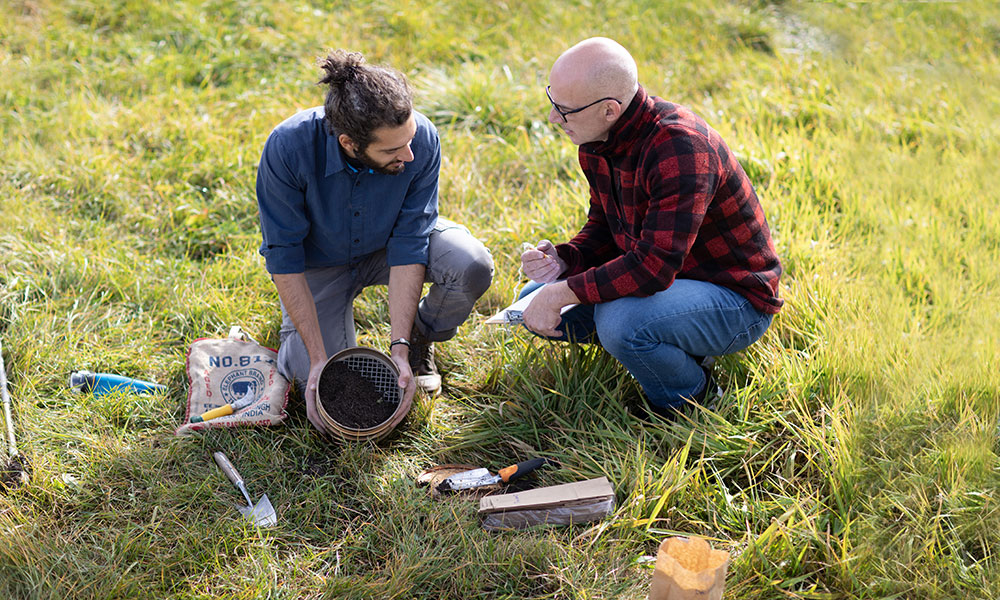 Men on ground surrounded by soil and tools