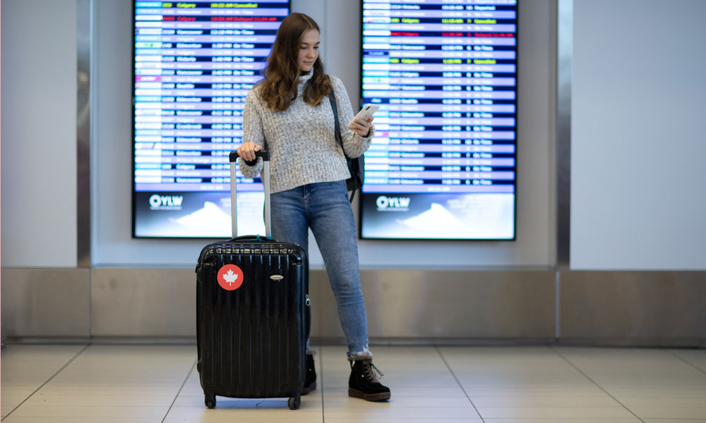 Girl standing in airport with suitcase