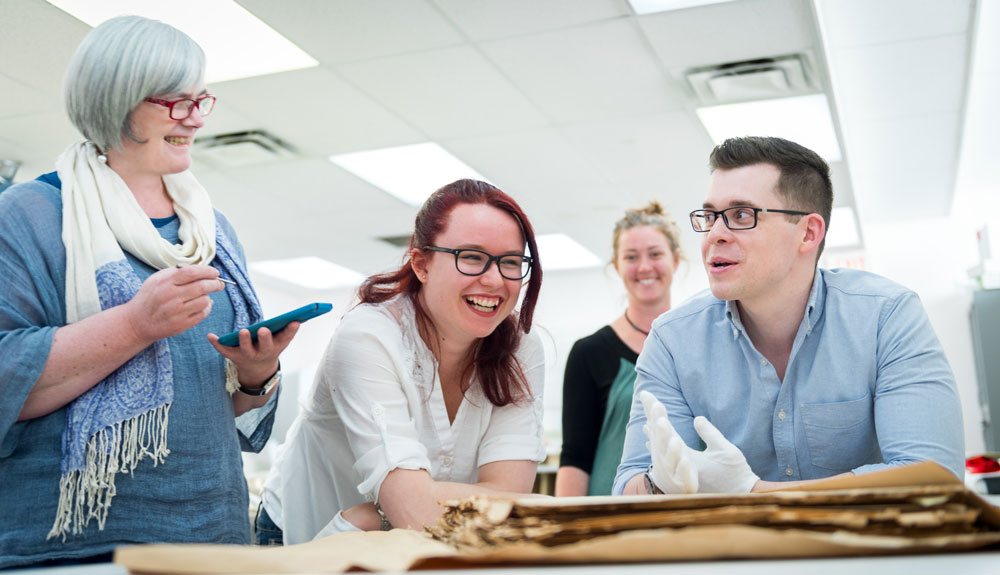 Prof. Catherine Higgs and students examining historical documents