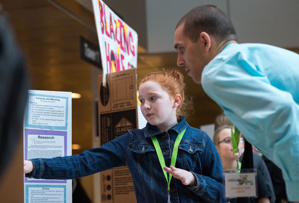 A young girl explains her science project at the Expo of awesome.