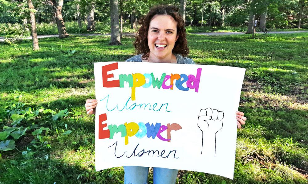 Tayana holding a sign: Empowered women empower women