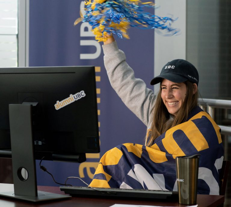 An excited, smiling UBCO alumnus watches the Homecoming celebration on her computer.