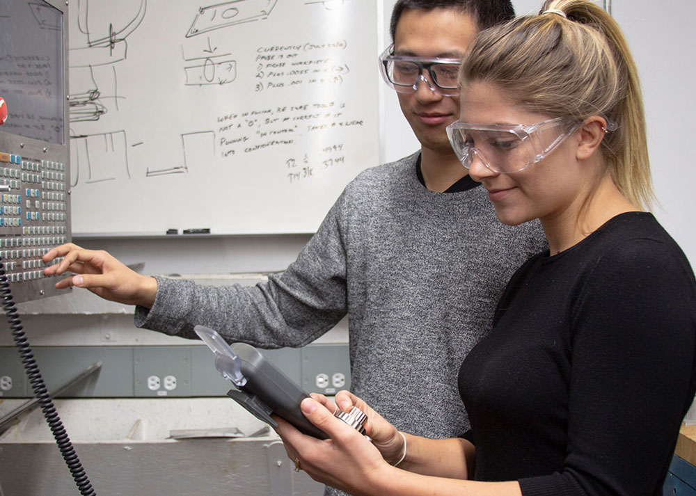 A student and a professor read a manufacturing device in a lab at UBC Okanagan