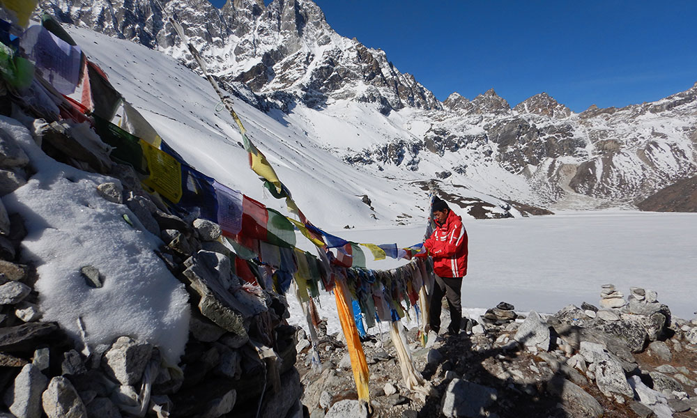 Man on mountain with Nepali prayer flags