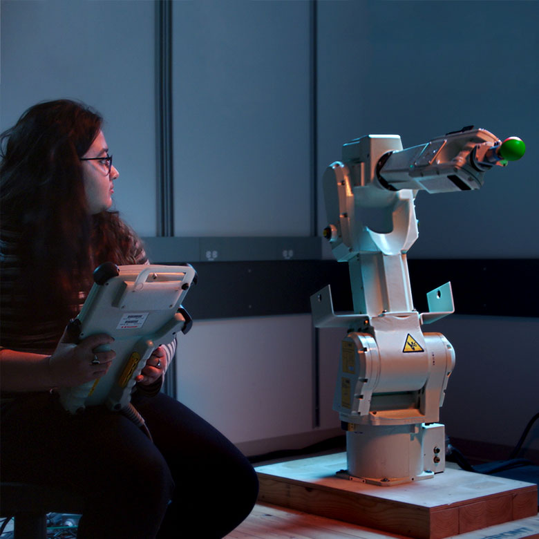 Girl controlling robotic arm through tablet