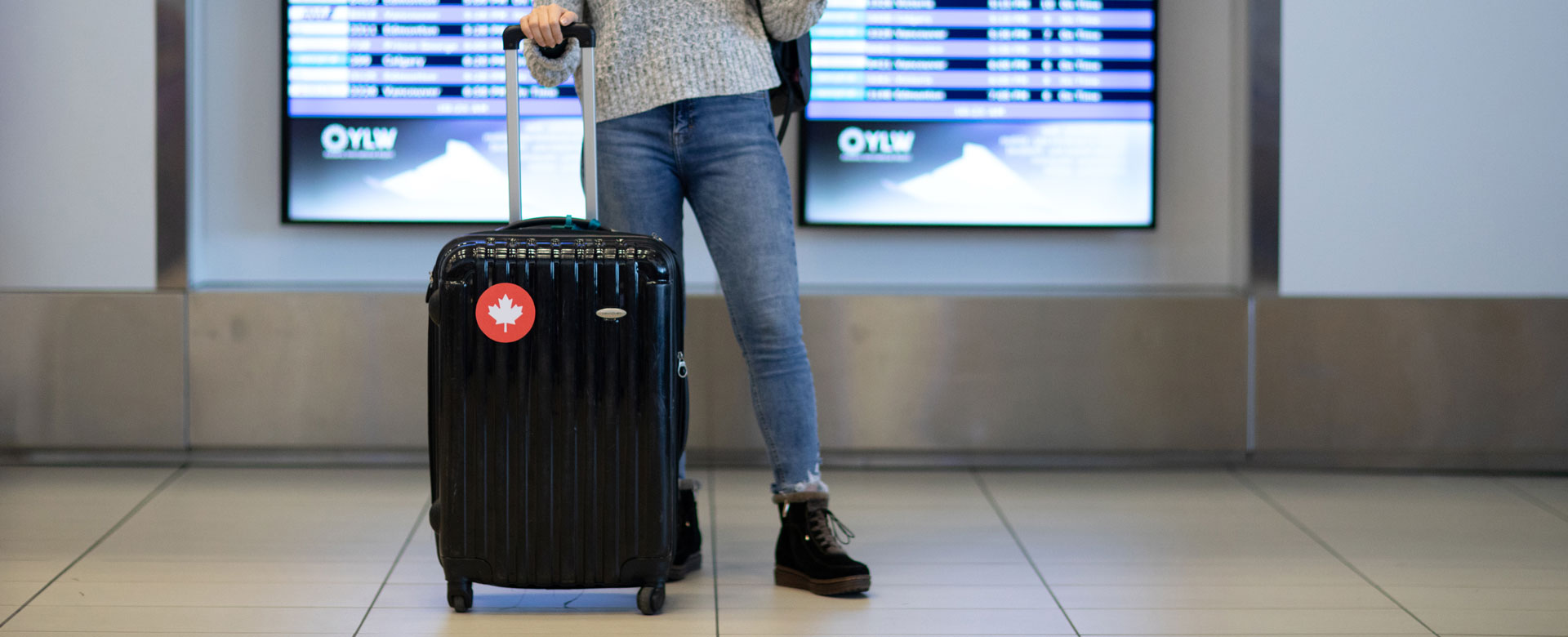 A student standing in the airport with their suitcase