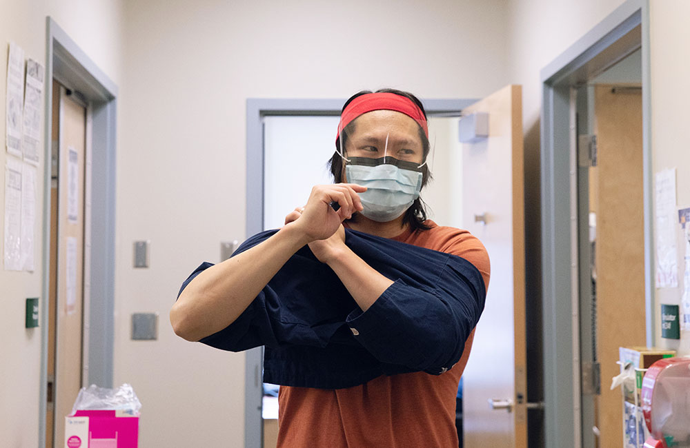 Dr. Huang putting on his scrubs for the start of his shift