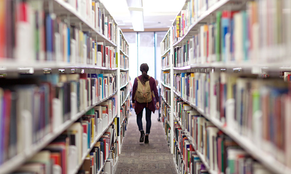 A student walking through library stacks